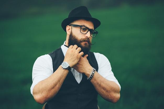 Mężczyzna z brodą i okularami na zielonym polu