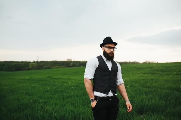 Mężczyzna z brodą i okularami przeciwsłonecznymi chodzi po polu