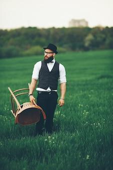 Mężczyzna z brodą i okularami przeciwsłonecznymi na zielonym polu