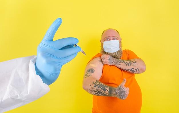 Mężczyzna z brodą i tatuażami robi szczepionkę przeciwko covid