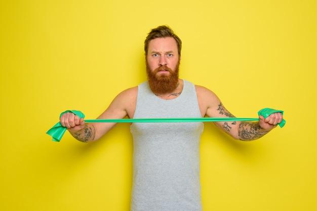 Mężczyzna z brodą i tatuażami trenuje z gumką