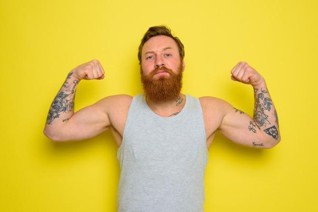 Mężczyzna z brodą i tatuażami z dumą pokazuje swoje mięśnie