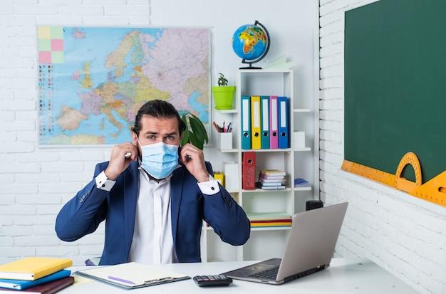 Mężczyzna z brodą i wąsami nosi maskę ochronną przed wirusem pandemicznym wygląda jak biznesmen lub nauczyciel w college'u lub szkole, edukacja na odległość z koronawirusem.
