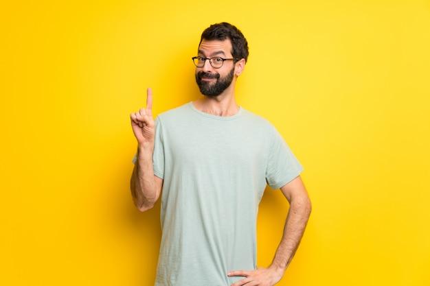 Mężczyzna z brodą i zieloną koszula pokazuje palec w znaku najlepszy i podnosi
