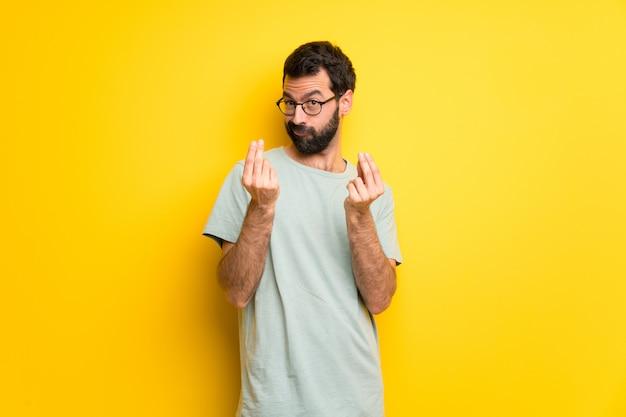 Mężczyzna z brodą i zieloną koszula robi pieniądze gestowi