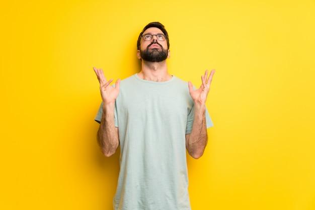 Mężczyzna z brodą i zieloną koszulą sfrustrowany złą sytuacją