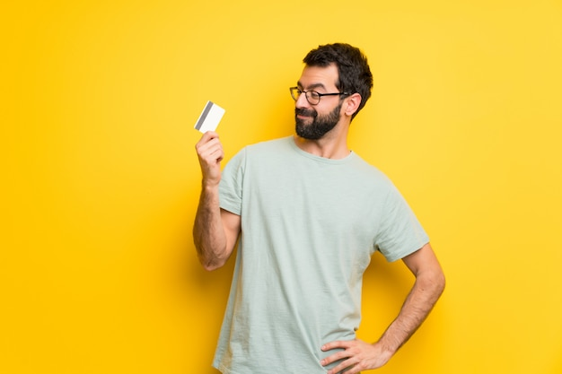 Mężczyzna z brodą i zieloną koszula trzyma kredytową kartę i główkowanie