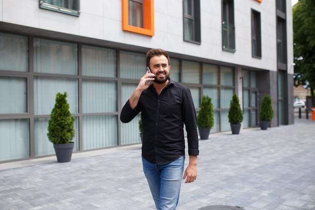 Mężczyzna z brodą idzie i mówi przez telefon
