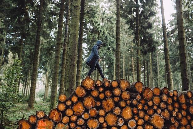 Mężczyzna z brodą idzie na drewno w lesie