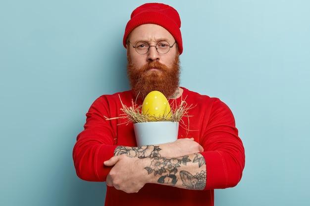 Mężczyzna z brodą imbir na sobie kolorowe ubrania i trzymając jajko wielkanocne