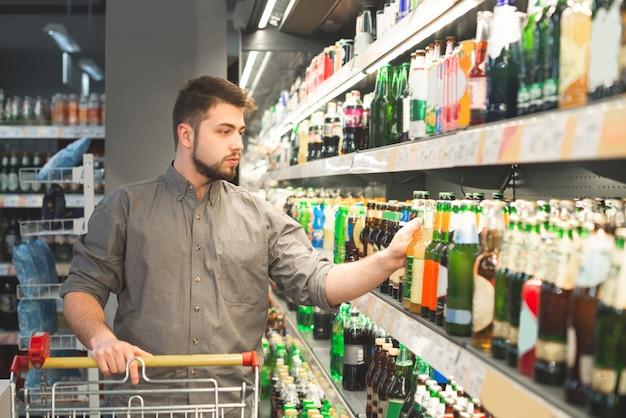 Mężczyzna z brodą kupuje piwo w supermarkecie, bierze butelkę z półki w dziale alkoholi