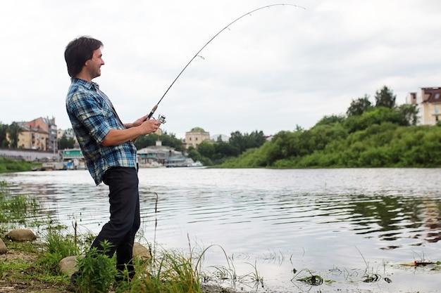 Mężczyzna z brodą łowi ryby na spinning w rzece
