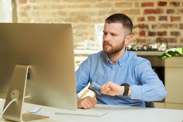 Mężczyzna z brodą marszczy brwi, patrząc na wyświetlacz komputera stacjonarnego i trzyma w domu kartę kredytową