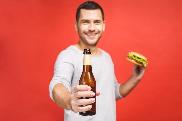 Mężczyzna z brodą na białym tle na czerwonym tle trzyma hamburgera i butelkę piwa, portret