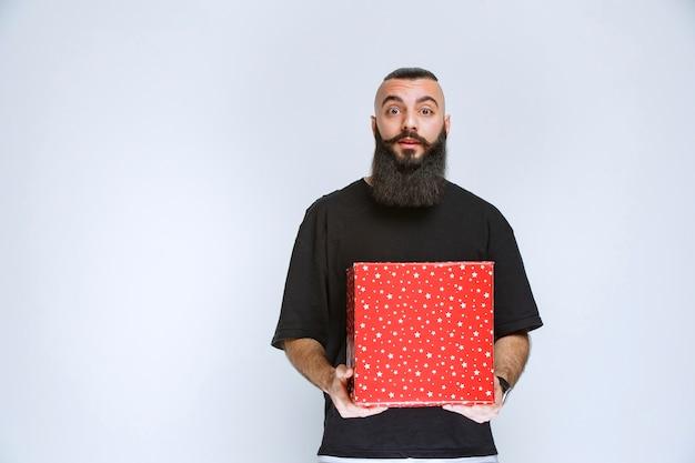 Mężczyzna z brodą oferujący czerwone pudełko na prezent