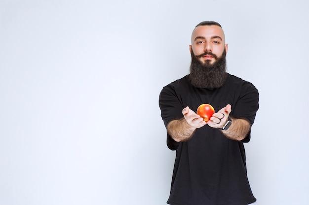 Mężczyzna z brodą oferuje czerwone jabłko lub brzoskwinię.