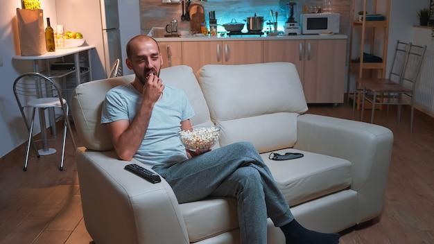 Mężczyzna z brodą ogląda program telewizyjny za pomocą pilota do zmiany kanałów w telewizji