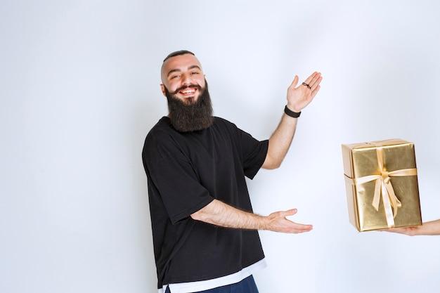 Mężczyzna z brodą otrzymujący pudełko upominkowe w kolorze złotym.