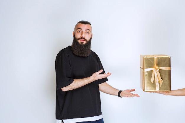 Mężczyzna z brodą pokazujący jego złote pudełko upominkowe.