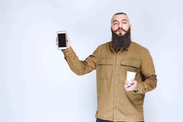 Mężczyzna z brodą pokazujący swojego smartfona, trzymając filiżankę kawy.