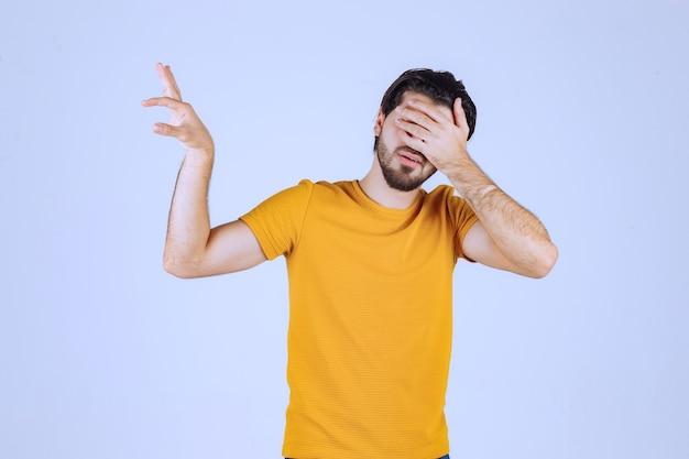 Mężczyzna z brodą pokazujący szacunkowe wymiary obiektu.