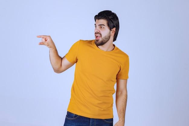 Mężczyzna z brodą pokazujący szacunkowe wymiary obiektu