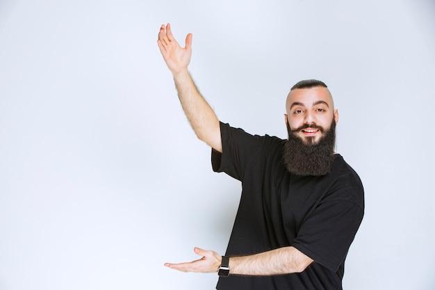 Mężczyzna z brodą pokazujący wymiary przedmiotu.