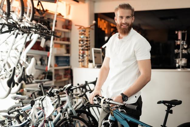 Mężczyzna z brodą pozuje z rowerem.