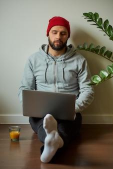 Mężczyzna z brodą pracuje na swoim laptopie