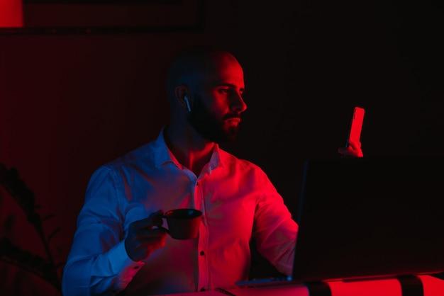 Mężczyzna z brodą pracuje zdalnie na laptopie w domu