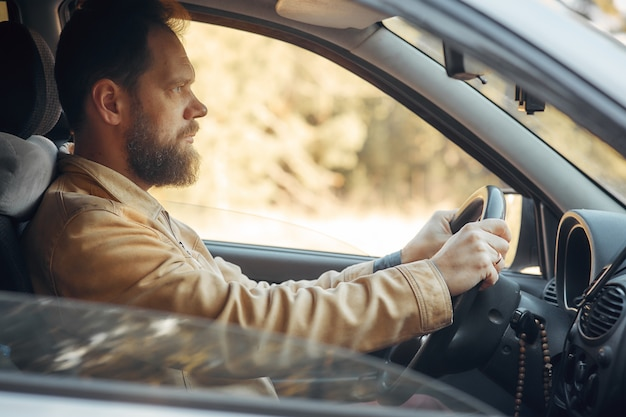 Mężczyzna z brodą prowadzący samochód