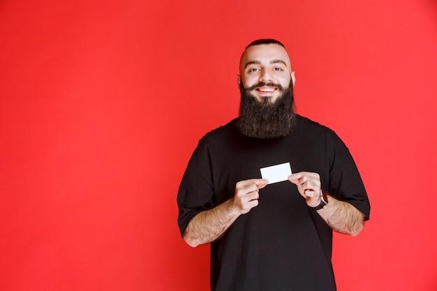 Mężczyzna z brodą przedstawia swoją wizytówkę.