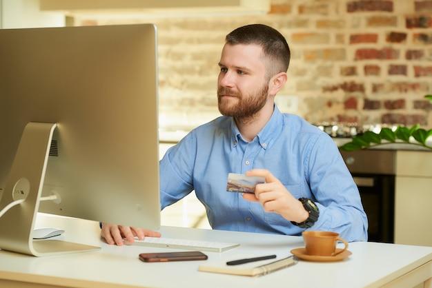 Mężczyzna z brodą siedzi przed komputerem i trzyma w domu kartę kredytową