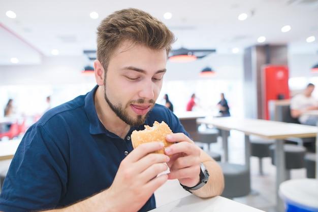 Mężczyzna z brodą siedzi w jasnej restauracji typu fast food i z apetytem patrzy na burgera w dłoniach