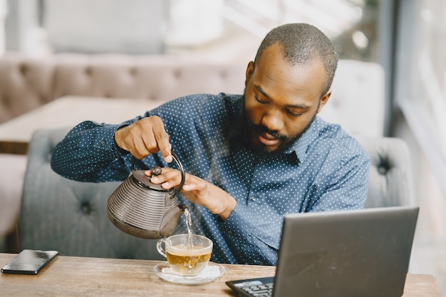 Mężczyzna z brodą siedzi w kawiarni i pije herbatę