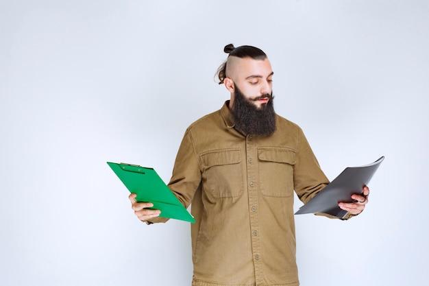 Mężczyzna z brodą sprawdza dwa różne projekty, aby wyłonić zwycięzcę.