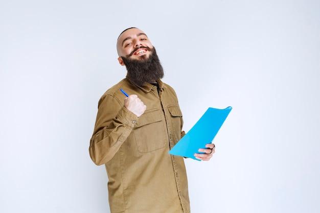 Mężczyzna z brodą sprawdza listę projektów i wygląda na zadowolonego.