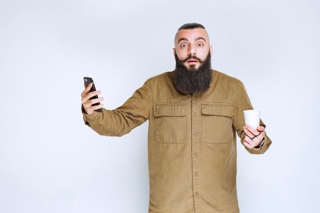 Mężczyzna z brodą sprawdza swoje wiadomości ze zdziwieniem.