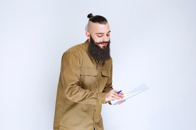 Mężczyzna z brodą sprawdzający listę projektów i zaznaczający notatki lub poprawki.
