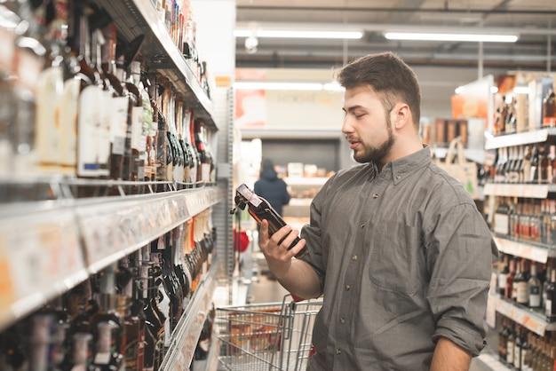 Mężczyzna z brodą stoi w supermarkecie z butelką koniaku w rękach