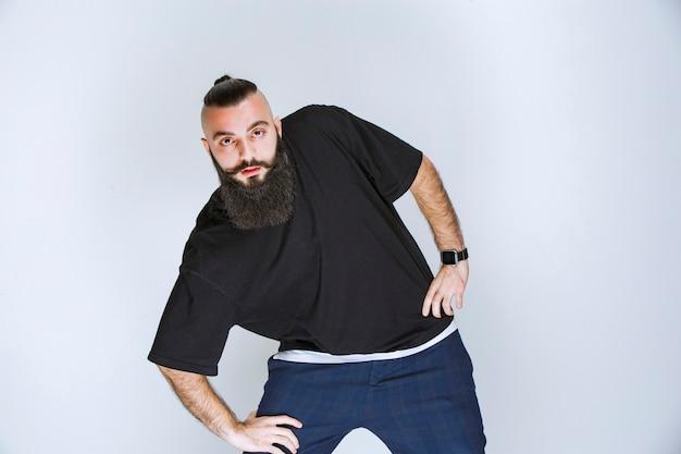 Mężczyzna z brodą tańczy lub daje niezwykłe pozy.