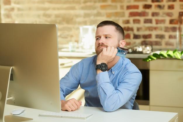 Mężczyzna z brodą tęskni przed komputerem i trzyma w domu kartę kredytową
