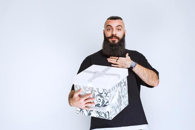 Mężczyzna z brodą trzyma białe niebieskie pudełko i wygląda na zaskoczonego.