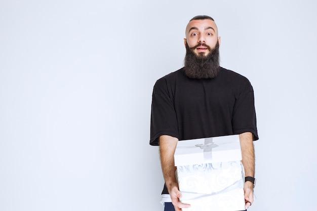 Mężczyzna z brodą trzyma białe niebieskie pudełko i wygląda na zdziwionego.