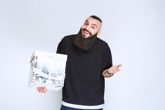 Mężczyzna z brodą trzyma białe niebieskie pudełko, uśmiechając się i czując się szczęśliwy.