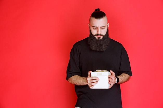 Mężczyzna z brodą trzyma białe pudełko i wygląda na niepewnego, co jest w środku.