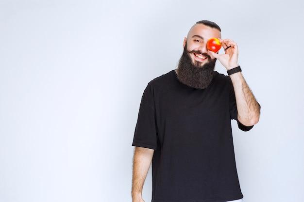 Mężczyzna z brodą trzyma czerwone jabłko lub brzoskwinię.