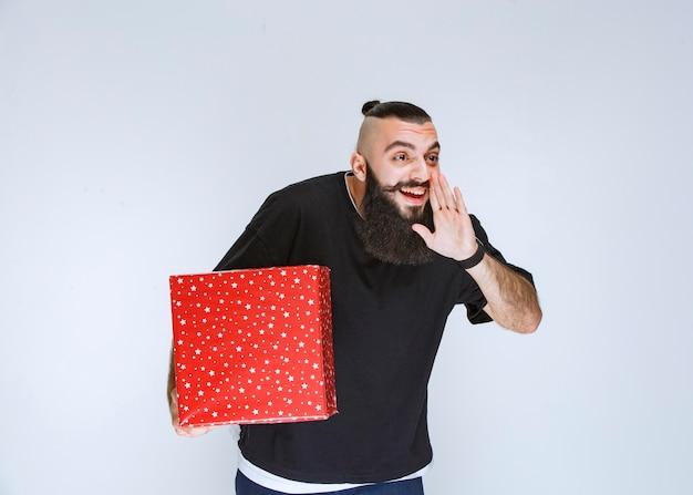 Mężczyzna z brodą trzyma czerwone pudełko i dzwoni do kogoś lub szepcze.