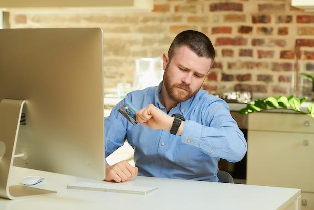 Mężczyzna z brodą trzyma kartę kredytową, patrząc na zegarek na rękę w domu