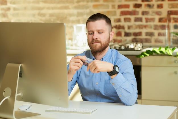 Mężczyzna z brodą trzyma kartę kredytową przygotowującą się do robienia zakupów online w domu